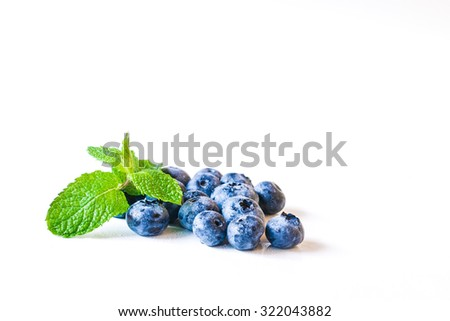 Fresh sweet blueberry fruit and leaf of mint.. Dessert healthy food. Group of ripe blue jui?y organic berries. Raw summer diet. Delicious nature vegetarian ingredient. Wooden background. - stock photo