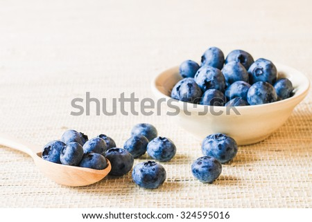 Fresh sweet blueberry fruit in wooden spoon. Dessert healthy food. Group of ripe blue juicy organic berries. Raw summer diet. Delicious nature vegetarian ingredient. Wooden background. - stock photo