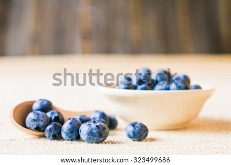 Fresh sweet blueberry fruit in wooden spoon. Dessert healthy food. Group of ripe blue juisy organic berries. Raw summer diet. Delicious nature vegetarian ingredient. Wooden background. - stock photo