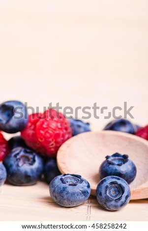 Fresh sweet blueberry, raspberry fruit. Dessert healthy food. Group of ripe blue juisy organic berries. Raw summer diet. Delicious nature vegetarian ingredient. Wooden background. - stock photo