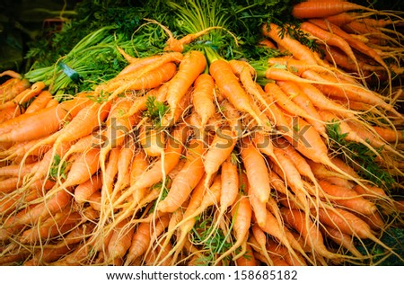 Fresh sweet carrots at local farmer market in Paris. Shadowed angles. - stock photo