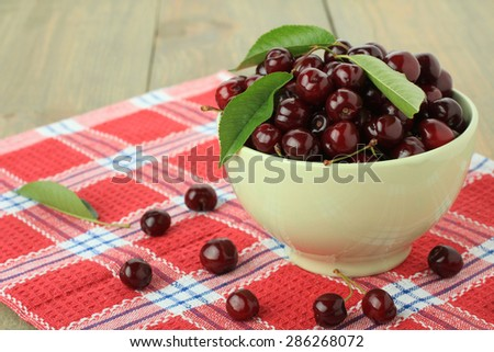 Fresh sweet cherries in a bowl on a napkin on wooden background