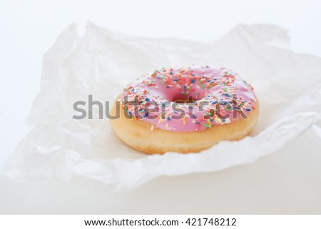 Fresh sweet colorful homemade pink donut on a white kitchen background for birthday or party, closeup, selective focus - stock photo