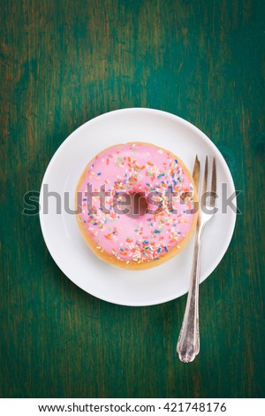 Fresh sweet colorful homemade pink donut with fork on a green wooden vintage background for birthday or party, top view, with free space for text - stock photo
