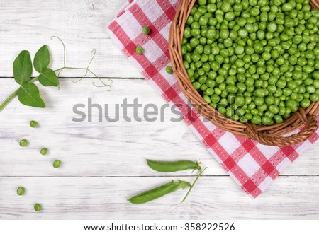 fresh sweet green peas in basket on wooden table top view - stock photo