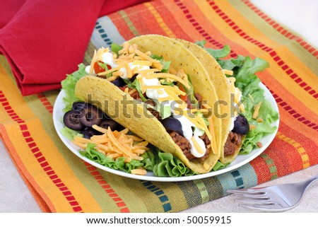 Fresh tacos with sour cream and cheese on a festive place mat. - stock photo
