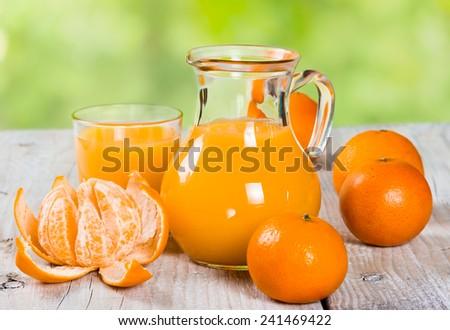Fresh tangerine juice on a wooden background - stock photo