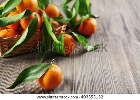 Fresh tangerines with leaves in basket on wooden table, closeup - stock photo