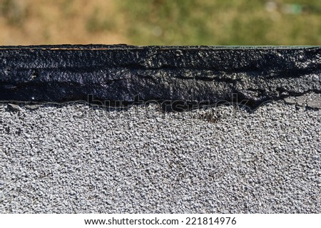 fresh tar roof wet patch along the edge of a flat roof - stock photo