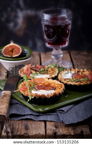 fresh tart or pie with figs, ham, goat cheese and thyme, served with a glass of red wine - stock photo