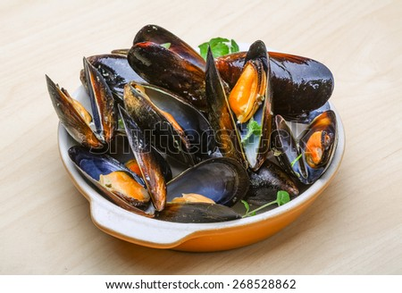 Fresh tasty Boiled mussels with herbs on wood background - stock photo