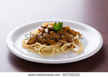 fresh tasty champignon mushroom spaghetti on a white plate - stock photo