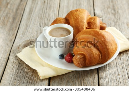 Fresh tasty croissants with berries and coffee on grey wooden background - stock photo