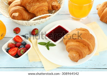 Fresh tasty croissants with berries on blue wooden background - stock photo