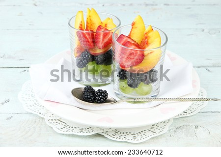 fresh tasty fruit salad on blue wooden table - stock photo