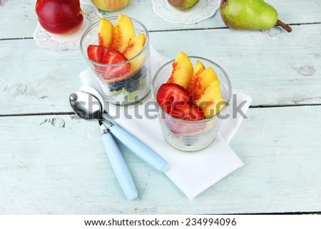 fresh tasty fruit salad on blue wooden table - stock photo