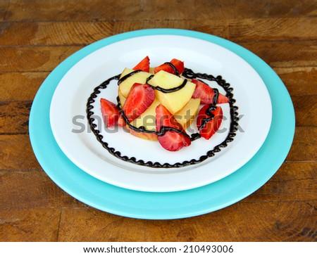 fresh tasty fruit salad on wooden table - stock photo