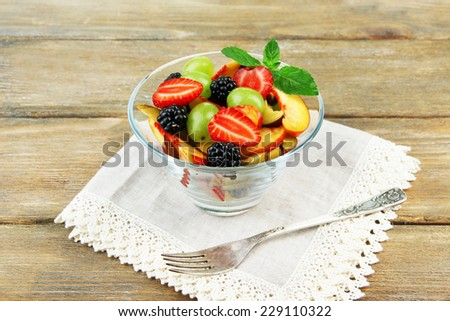 fresh tasty fruit salad on wooden table - stock photo