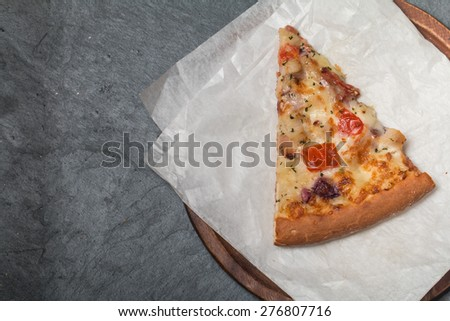 Fresh tasty pizza slices on black background, top view - stock photo