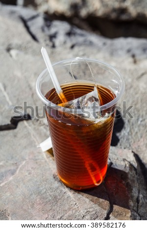 fresh tea in a disposable plastic cup with a spoon and a bag on a rock on the nature background - stock photo