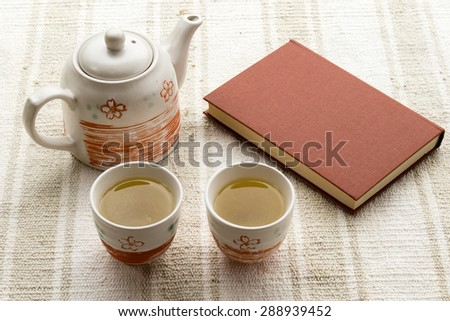 fresh tea in cup and book on garden table - stock photo