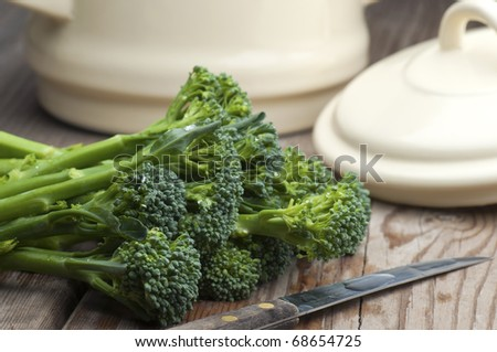 Fresh Tenderstem Broccoli Laid On A Wooden Kitchen Table With A Vegetable Knife and A Pan With Lid In The Background