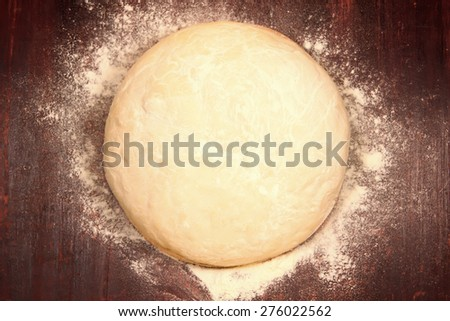 fresh the dough is ready for baking on wooden background with flour - stock photo