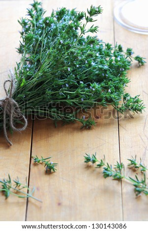 Fresh thyme bouquet on a wooden board. - stock photo