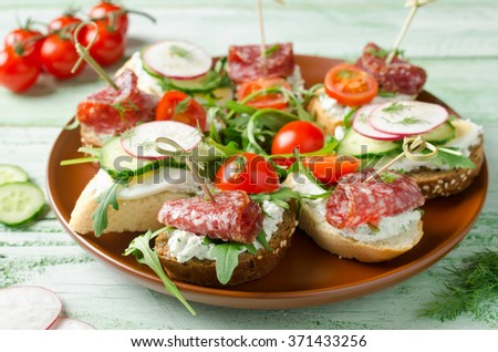 Fresh toast sandwiches with cottage cheese, egg, radish, cucumber, salami, cherry tomatoes and arugula - stock photo
