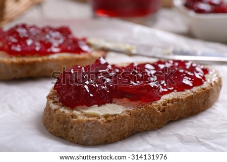 Fresh toast with butter and jam on table close up - stock photo