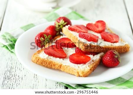 Fresh toast with strawberry on white wooden background - stock photo