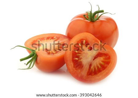 fresh tomato and a cut one on a white background - stock photo
