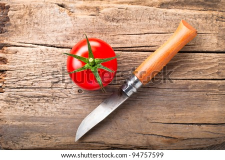 Fresh tomato and steel knife on vintage wooden cutting board - stock photo