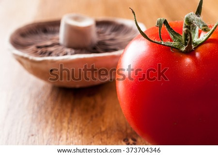 Fresh Tomato in he foreground with a mushroom out of focus in the background