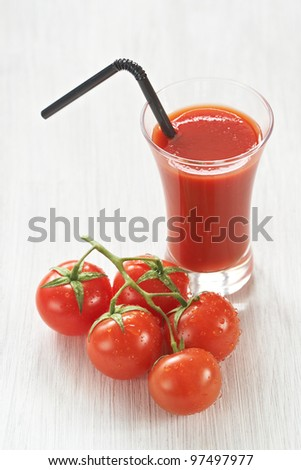 Fresh tomato juice and ripe cherry tomatoes on white wood table
