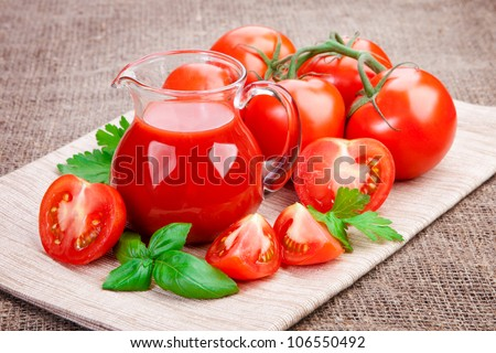 Fresh tomato juice in a pitcher on the table. Ripe tomatoes and basil leaves - stock photo