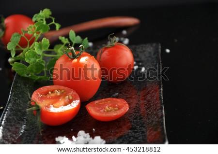 Fresh tomato on black plate with sea salt on background - stock photo