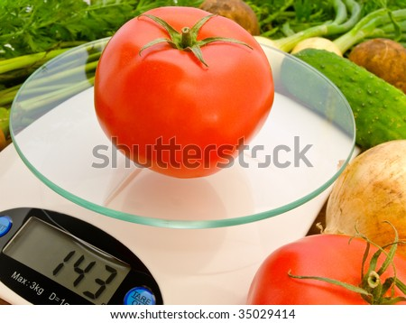 fresh tomato on the scales that show the weight in grams - stock photo