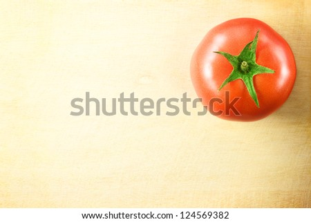 fresh tomato on wooden cutting board - stock photo