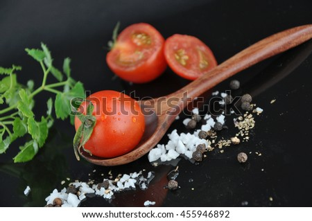 Fresh tomato on wooden spoon with sea salt and black pepper on background - stock photo