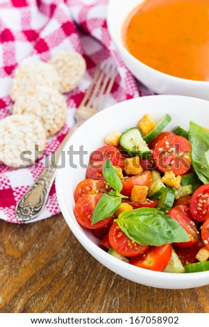 Fresh tomato salad with cucumber and croutons - stock photo