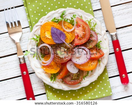 Fresh tomato salad with red onion, basil and chia seeds closeup. - stock photo