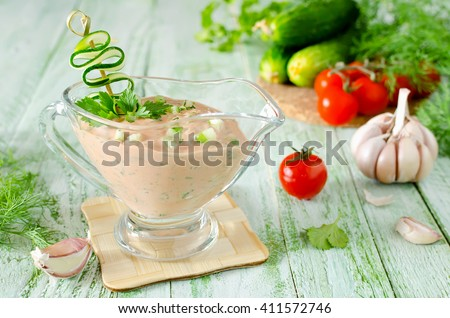 Fresh tomato sauce for meat on a wooden table. Sauce made from fresh tomatoes, cucumber, mayonnaise, paprika, garlic, herbs and hot peppers - stock photo