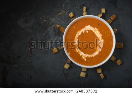 Fresh tomato soup in white bowl on dark metal background - stock photo