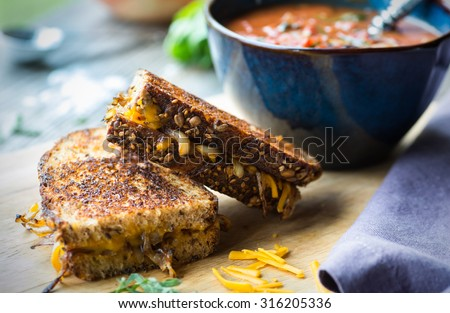 Fresh tomato soup with grilled onion and cheese sandwich - stock photo