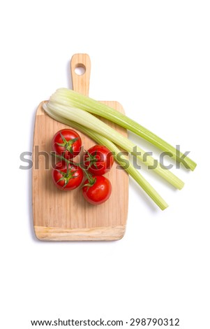 Fresh tomatoes and celery sticks on chopping board, top view isolated on white background  - stock photo