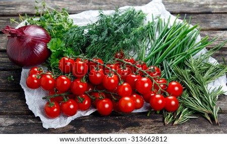 Fresh Tomatoes and Green Vegetables. Onion, Dill, Rosemary, Parsley, Chives and thyme. on old wooden table. - stock photo