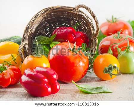 Fresh tomatoes and peppers  on a wooden table - stock photo
