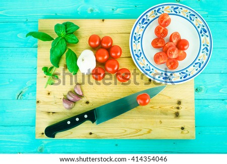 Fresh tomatoes basil and garlic as pasta sauce ingredients top view on rustic wooden chopping board and aquamarine background  - Concept of healthy food  typical of mediterranean diet  - stock photo