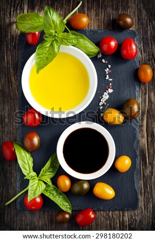 Fresh tomatoes, basil, olive oil and balsamic vinegar on wooden  - stock photo